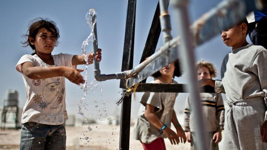 Un grupo de niños recoge agua de un punto de distribución en el campo de refugiados de Za'atari (Jordania)