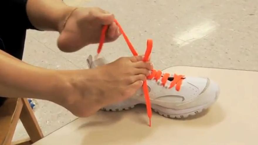 Retrona sin brazos ata los cordones de unas zapatillas con los pies