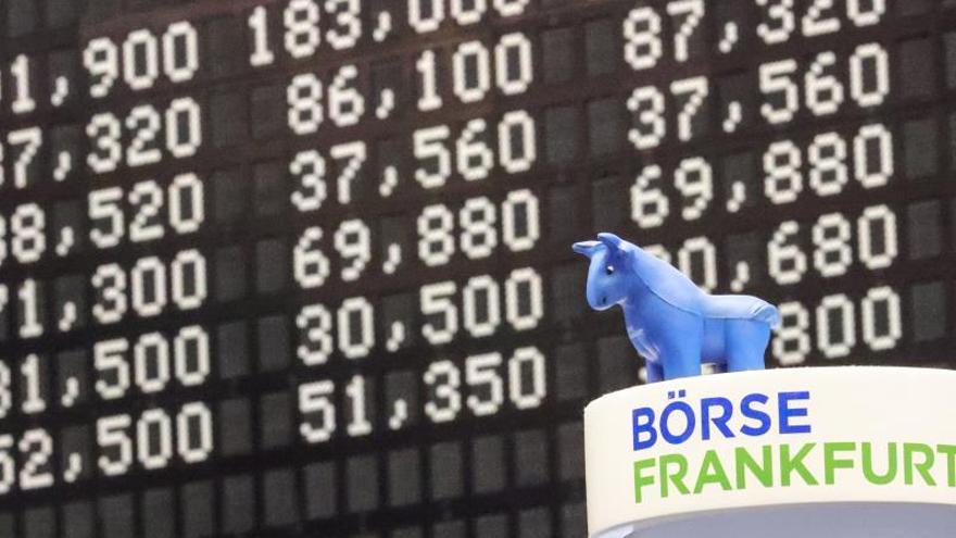 Vista del muñeco de un toro junto a los resultados de los índices en la Bolsa de Valores de Fráncfort.