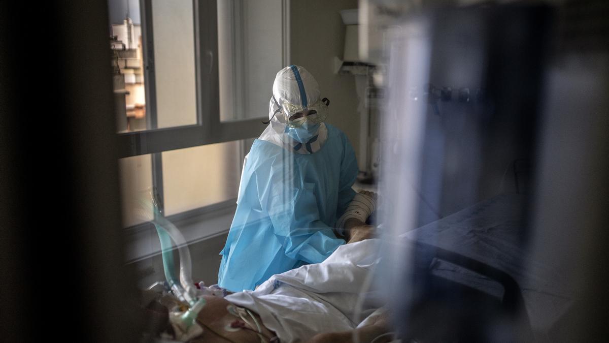 Una fisioterapeuta trata a un paciente con COVID-19 en la UCI del hospital. Los pacientes que pasan muchas semanas ingresados necesitan que les ejerciten las articulaciones.