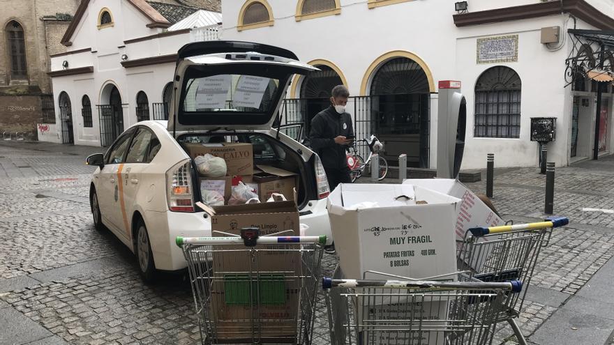 Un taxi carga las cajas de comida para el reparto/Foto: C.I.