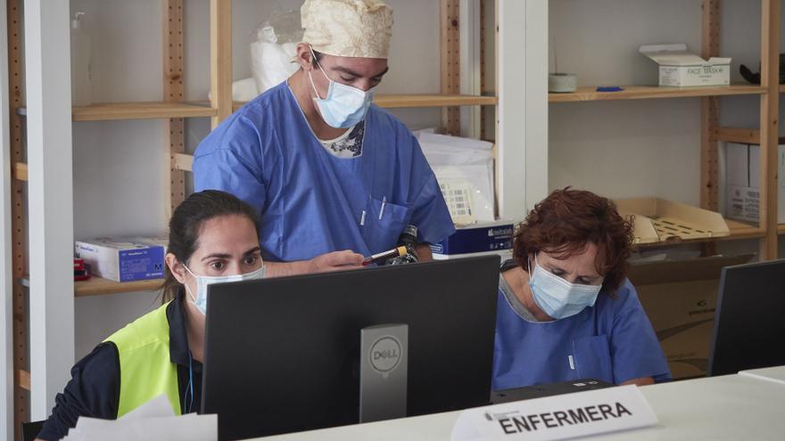 Trabajadores sanitarios protegidos atienden a los pacientes que acuden para realizarse una extracción de muestras en el recinto ferial REFENA de Pamplona.