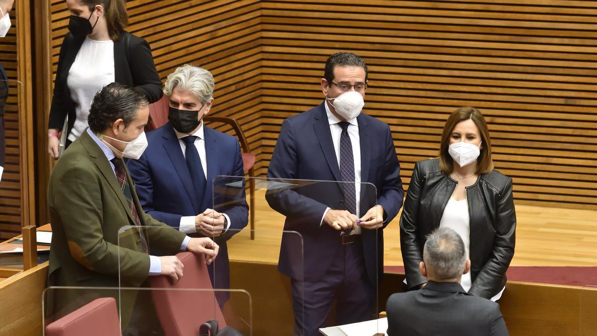 Un grupo de diputados del PP charla antes de sentarse en su escaño en las Corts Valencianes.