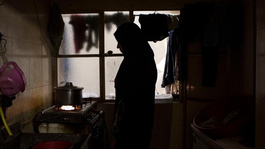 """Un rayo de luz entra a través de una ventana oxidada e ilumina la silueta de 'L', madre siria de seis hijos. L. huyó de la guerra de Siria hace un año. """"Había demasiado sufrimiento, demasiado dolor..."""". Decidió trasladarse al campamento de Shatila con su familia para poder encontrar un lugar en el que vivir costeando un alquiler asequible. Paga casi 300 dólares (284 euros). Fuera del campo de refugiados es muy difícil encontrar un lugar para vivir por menos de 800 dólares (759 euros). Su marido encuentra empleo en trabajos temporales pero no gana lo suficiente como para alimentar a la familia. L. acude de manera regular al centro de salud de MSF en Shatila buscando atención médica para su familia. Fotografía: Diego Ibarra Sánchez"""