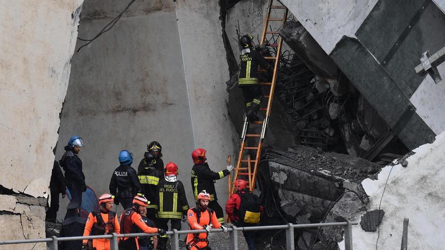 Miembros de los servicios de emergencia buscan entre los escombros tras derrumbarse unasección del viaducto Morandi en Génova este martes