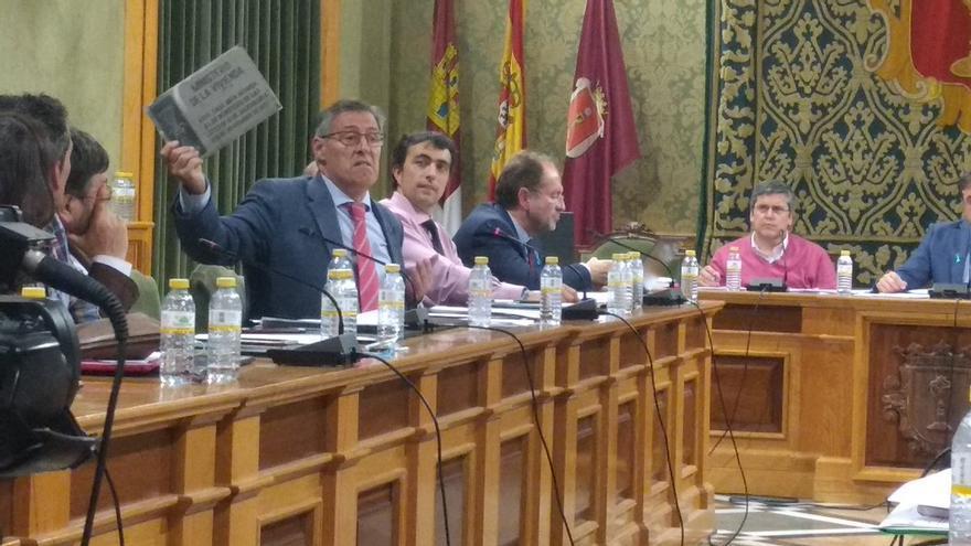 El concejal del PP de Cuenca, Carlos Navarro, esgrime una foto de una placa con el yugo y las flechas
