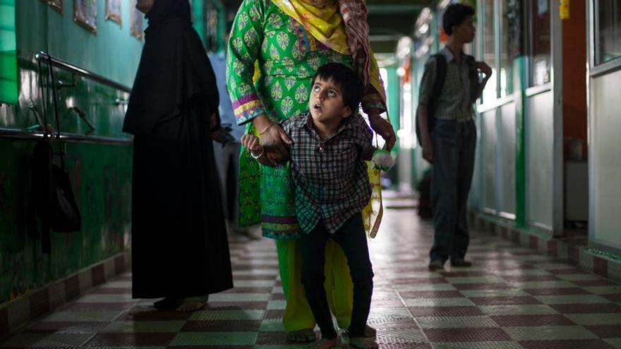 Prachi solo puede andar con la ayuda de brazos amigos. Nunca aprendió a hablar y lleva un guante en su mano izquierda para evitar mordérsela. Ella es una de los muchos niños que siguen naciendo con problemas en Bhopal / FOTO: Bernat Parera