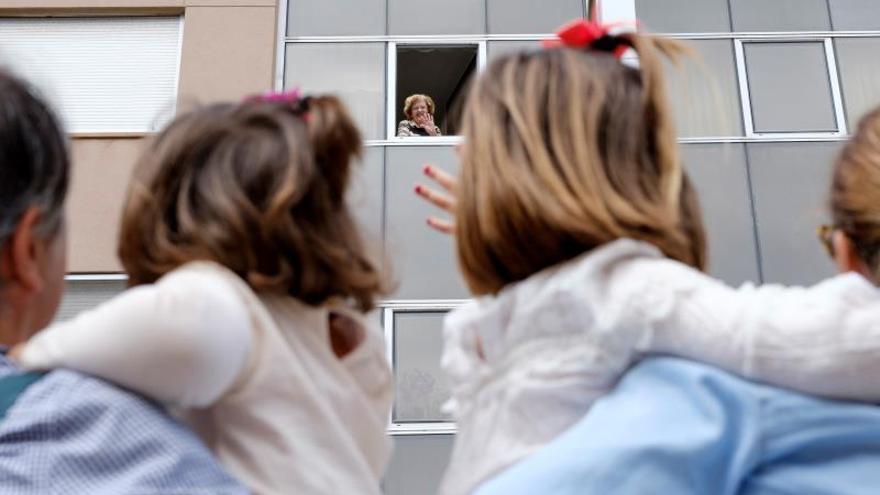 Teresa (i) y Carolina (d) aprovechan su salida a la calle para saludar a su abuela, Rosario, que les devuelve el saludo desde su ventana, esperando el día que pueda darles un abrazo.