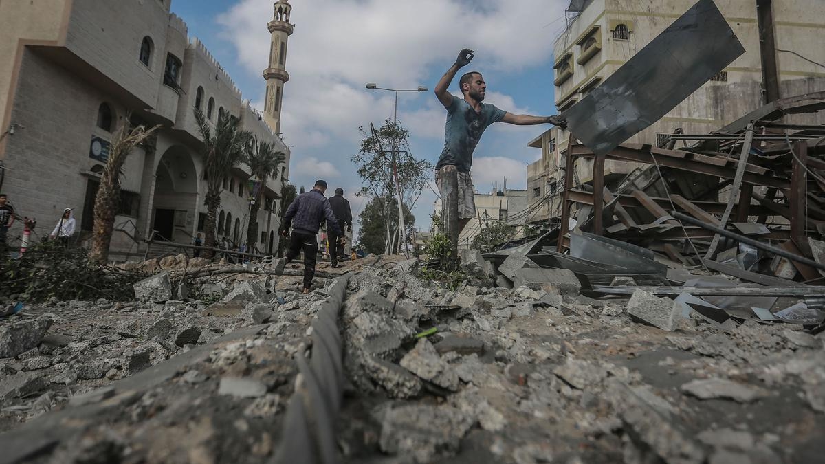 Hombres palestinos inspeccionan los escombros de una instalación destruida en el vecindario de Shejaiya después de un ataque aéreo israelí.