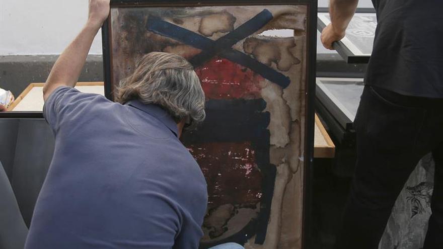 Un socio del Ateneo de La Laguna intenta proteger la tela de un cuadro que se ha roto en el incendio desatado esta tarde en el interior del edificio, cuyo tejado se ha derrumbado completamente. EFE/ Cristóbal García