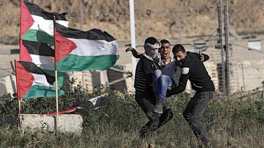 Varios manifestantes palestinos retiran a un joven que resultó herido en la frontera entre Israel y Gaza, el 31 de marzo de 2018
