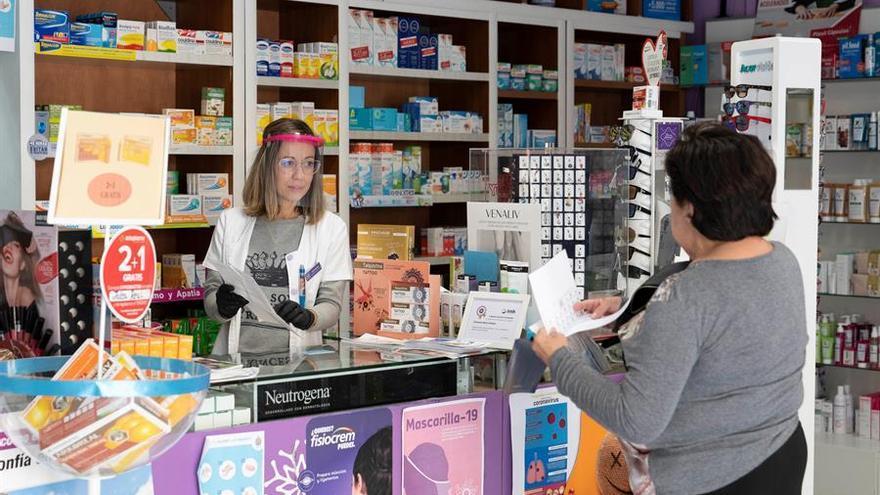 Una empleada de la farmacia del barrio de María Jiménez de la capital tinerfeña atiende al público protegida por una máscara facial.