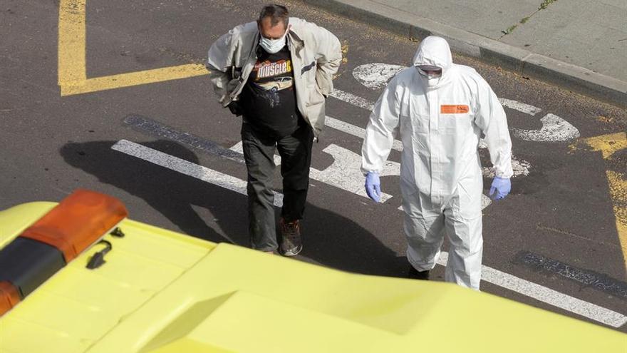 Un hombre que presentaba síntomas de COVID-19 es atendido este domingo en Santa Cruz de Tenerife por personal sanitario y trasladado en ambulancia a un centro hospitalario.