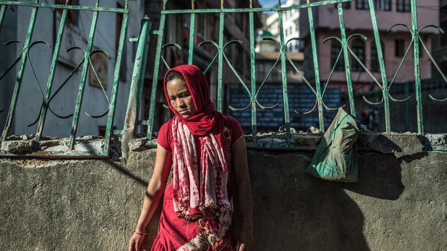 Tika Thapamagar frente a su vivienda destruida ahora vive junto a sus dos hijos y su marido Ramesh en el campo de desplazados de Tundhikel./ Pablo Tosco (Intermón Oxfam).