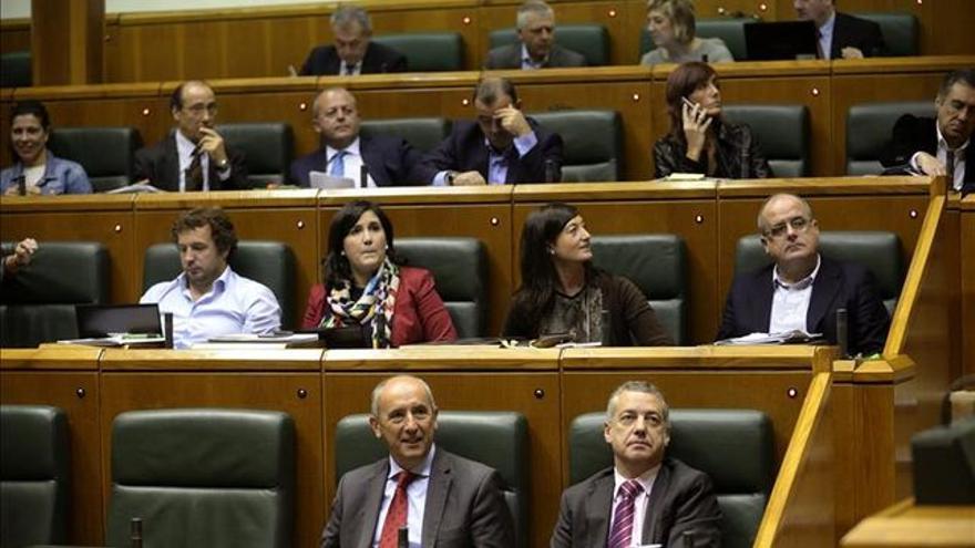 Varios parlamentarios consultan su equipo informático en un pleno de la Cámara