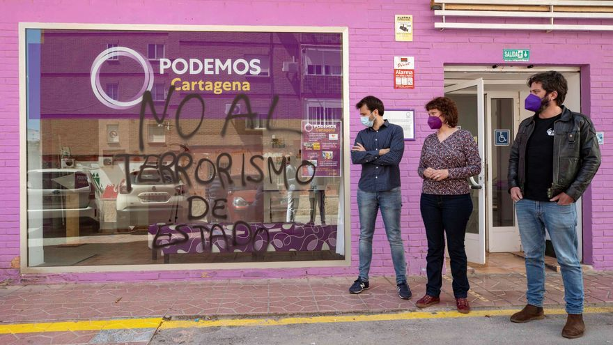 El diputado en el Congreso de Podemos Javier Sánchez Serna y la portavoz del parlamento murciano María Marín junto a una de las pintadas en la sede del partido en Cartagena.