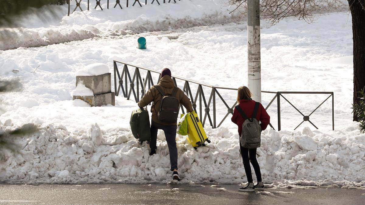 Dos personas avanzan entre la nieve llevando maletas en Madrid, tras el paso del temporal Filomena.