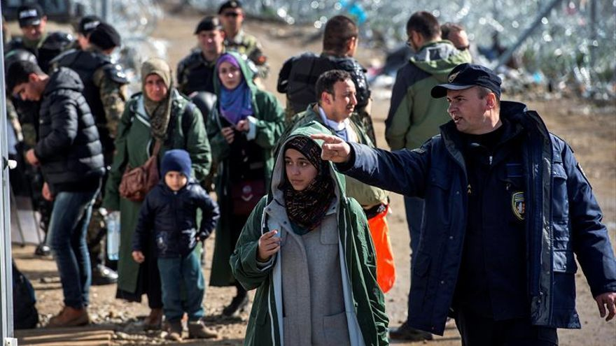 Un policía macedonio indica a una mujer refugiada dónde dirigirse tras cruzar la frontera griega cerca de la localidad de Gevgelija  Efe