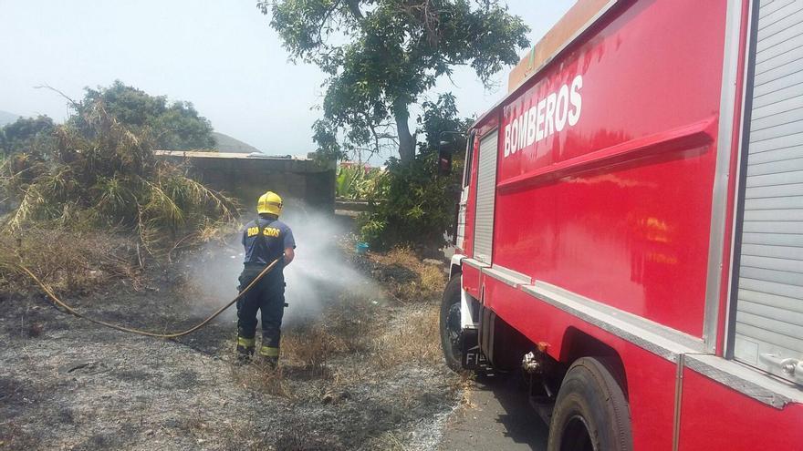 En la imagen, un bombero apaga el conato de incendio registrado este sábado en la zona la Calle Armas-Camino Los Barros del municipio de Los Llanos de Aridane. Foto:  BOMBEROS LA PALMA.