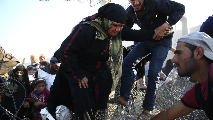Una mujer mayor siria pasa al lado turco de la frontera ayudada por dos hombres. Cientos de personas se amontonaban en la alambrada pidiendo auxilio a los soldados turcos que tenían la orden de frenar su entrada, aunque finalmente abrieron el paso, según informa EFE. /  (AP Photo/Lefteris Pitarakis)