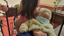 Eleonor con su muñeco bebé, protegido por mascarilla.