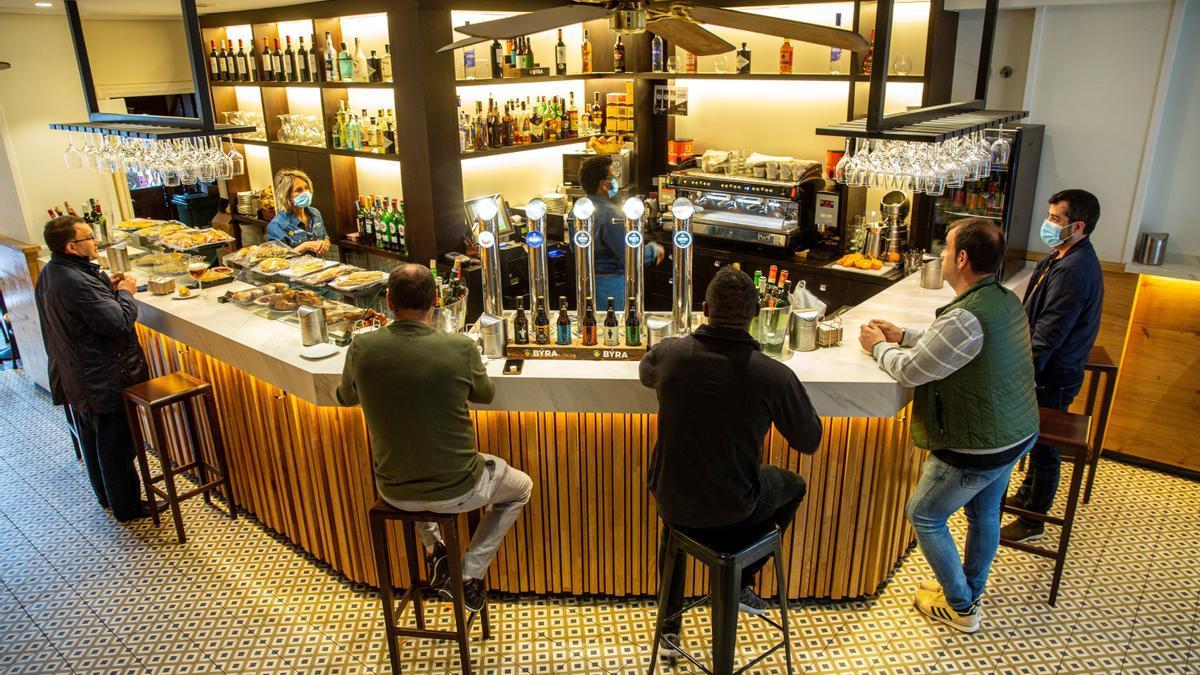 Clientes de un bar del centro de Vitoria toman café en la barra.