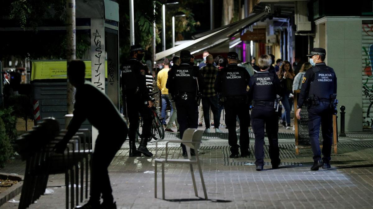Agentes de la Policía Local de Valencia recorren las terrazas de una conocida zona de ocio de la ciudad vigilando que se cumplen los horarios de cierre y las medidas ante la Covid-19 a poco minutos de la entrada en vigor del toque de queda. EFE/Manuel Bruque