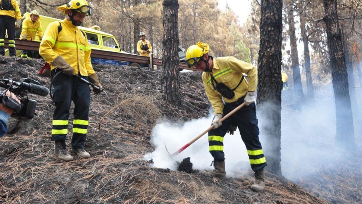 Bomberos apagando un rescoldo en un incendio en Gran Canaria
