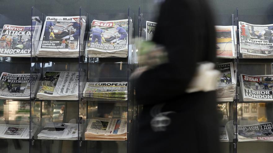 Un hombre pasa frente a un kiosco de prensa en Londres con noticias del atentado.