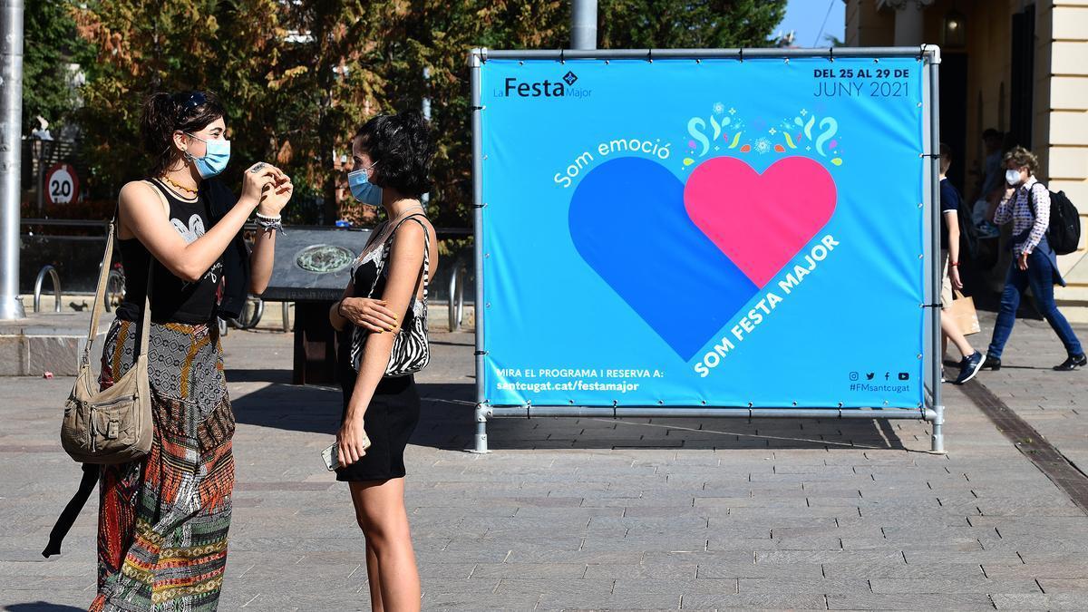 Dos jóvenes junto al cartel que anuncia la fiesta mayor de Sant Cugat