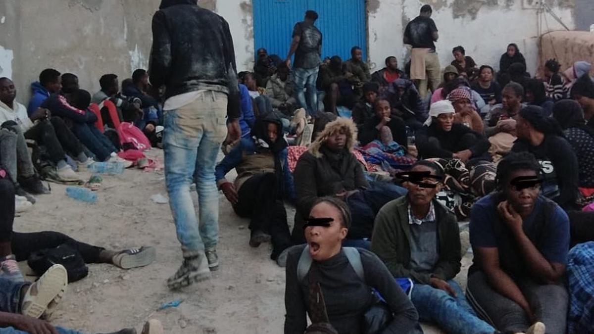 Hombres, mujeres y niños migrantes esperan frente al cuartel del peñón de Vélez de la Gomera
