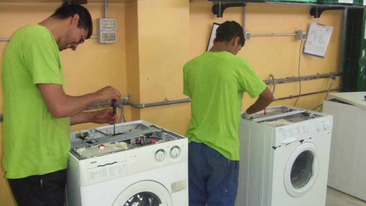 Trabajadores de una de las entidades de AERESS arreglan unas lavadoras para darles un segundo uso. / AERESS