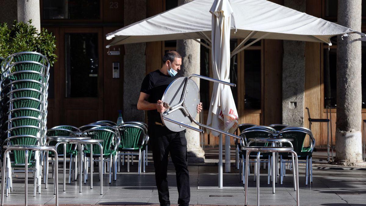 Un camarero coloca las mesas en una terraza