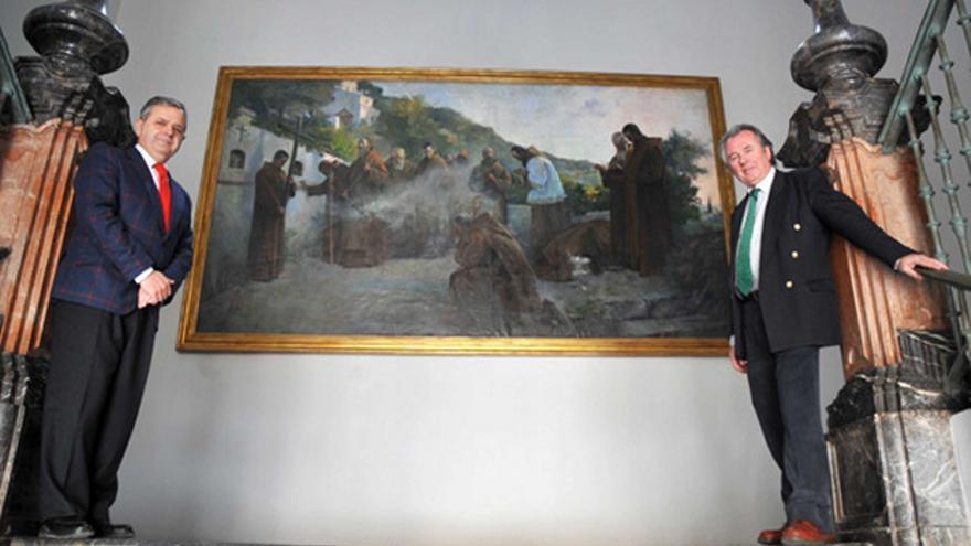 Salvador Fuentes y Manuel Gutiérrez, ante el cuadro restaurado.