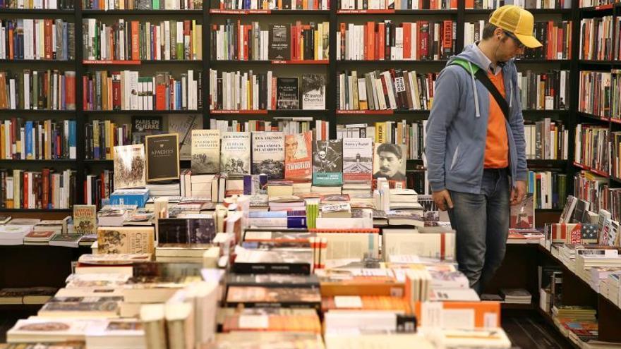 Un hombre observa libros en una librería.