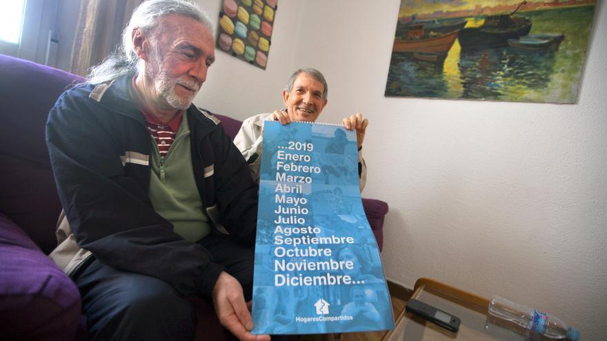 Félix (izquierda) y Luis muestran un calendario de la ONG en una de las casas de Hogares Compartidos