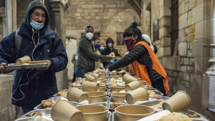 Ahmed recoge su plato antes de sentarse en la mesa del claustro de Santa Anna, en Barcelona