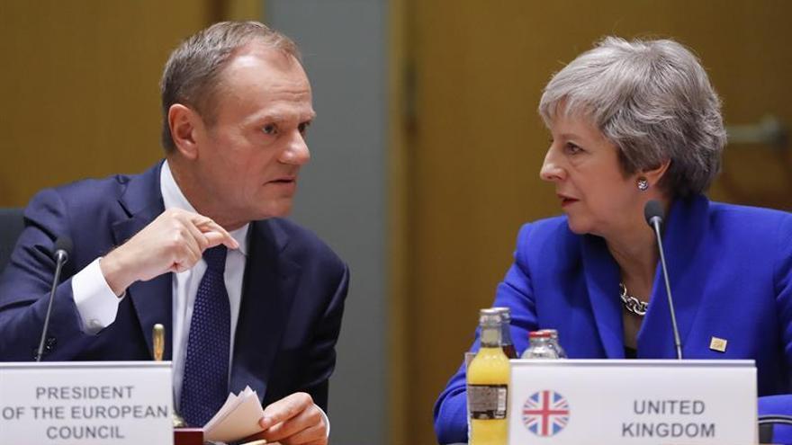 El presidente del Consejo Europeo, Donald Tusk, conversa con la primera ministra británica, Theresa May.