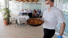 Un camarero sirve una paella en un restaurante de Valencia.