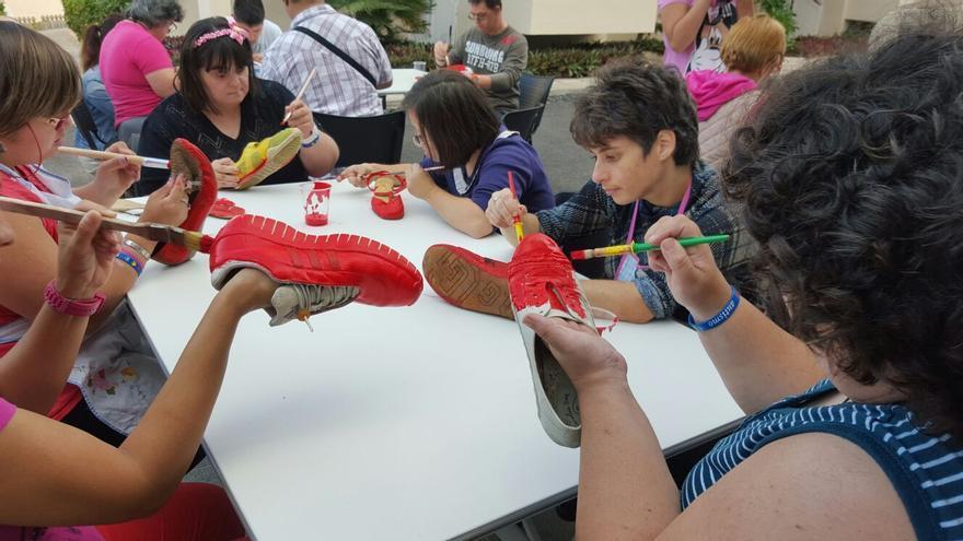 Miembros del colectivo de Padisbalta en el taller de zapatos rojos.