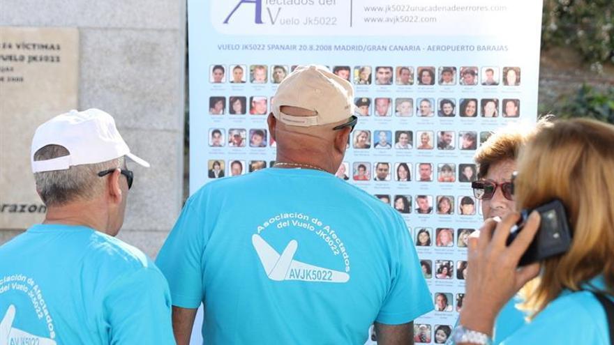 Miembros de la Asociación de Afectados del Vuelo JK5022 de Spanair observan las fotografías de las víctimas, durante el homenaje ante el Monumento en memoria de los pasajeros del JK5022, en el Parque Juan Carlos I de Madrid