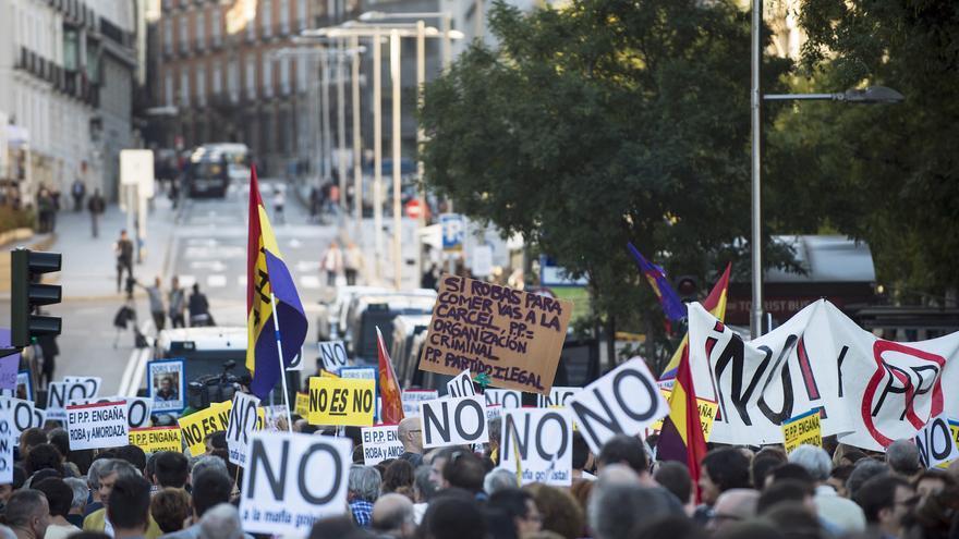 Centenares de personas se encaran a las vallas que impiden acceder a la Plaza de las Cortes, para mostrar su rechazo a investir presidente a Mariano Rajoy