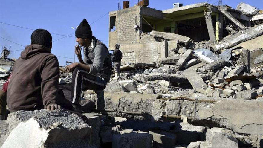 Dos adolescentes fuman junto a los escombros de un edificio en el distrito este de Mosul, Irak.