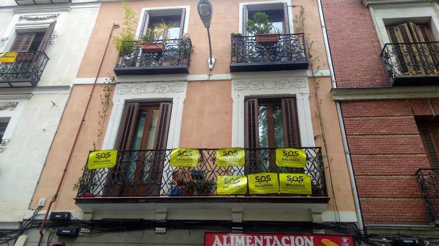 Carteles de 'SOS Malasaña' en un balcón del Dos de Mayo visibilizando el hartazgo vecinal con los problemas que acucian al barrio | SOMOS MALASAÑA