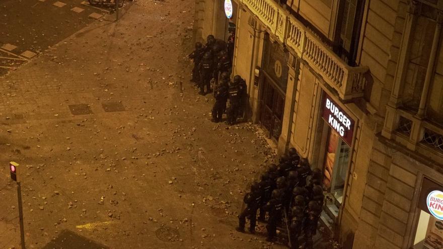 Agentes de la Policía Nacional parapetados en una esquina en la quinta noche de protestas en Barcelona.