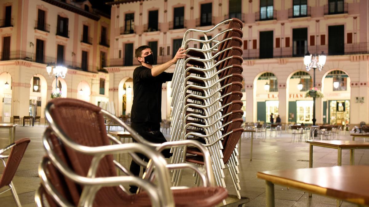 Un hostelero recoge la terraza de su establecimiento de Huesca. EFE/ Javier Blasco/Archivo
