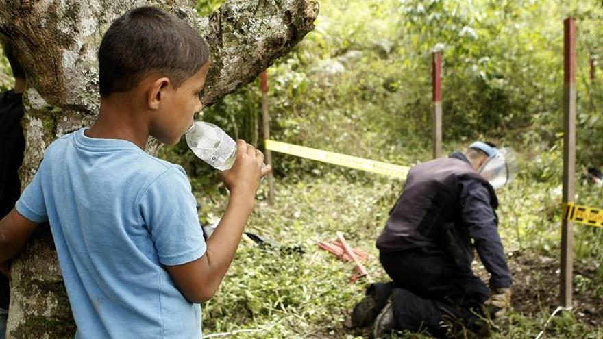 Un niño observa cómo un operario realiza labores de desminado en Colombia