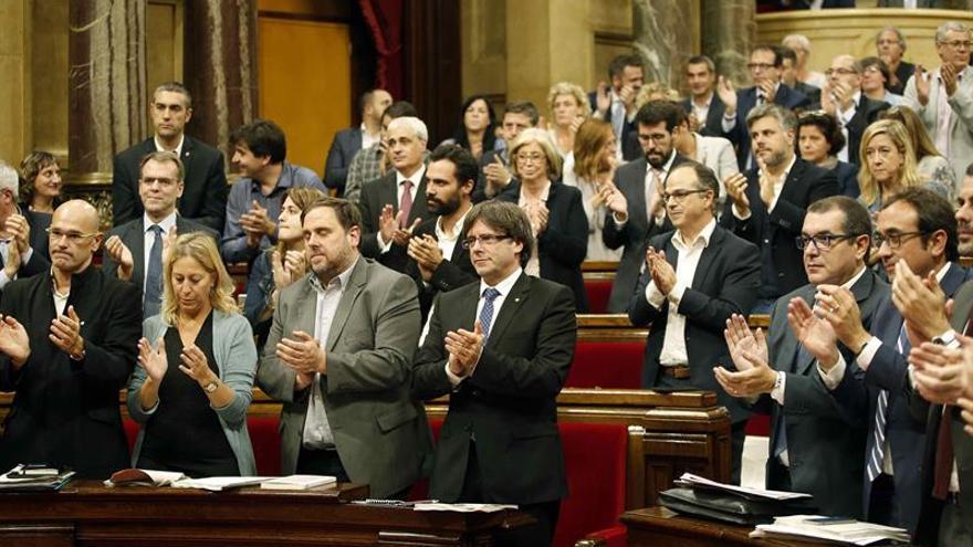 Diputados independentistas aplauden en el pleno tras aprobar la celebración de un referéndum