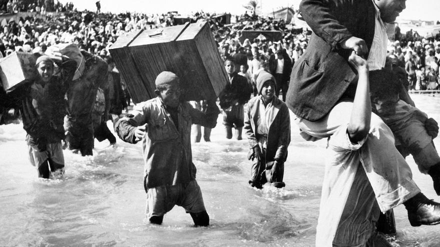 Palestinos desplazados inicialmente al campamento de Beach en Gaza abordan barcos hacia el Líbano o Egipto durante la primera guerra Árabe-Israelí.