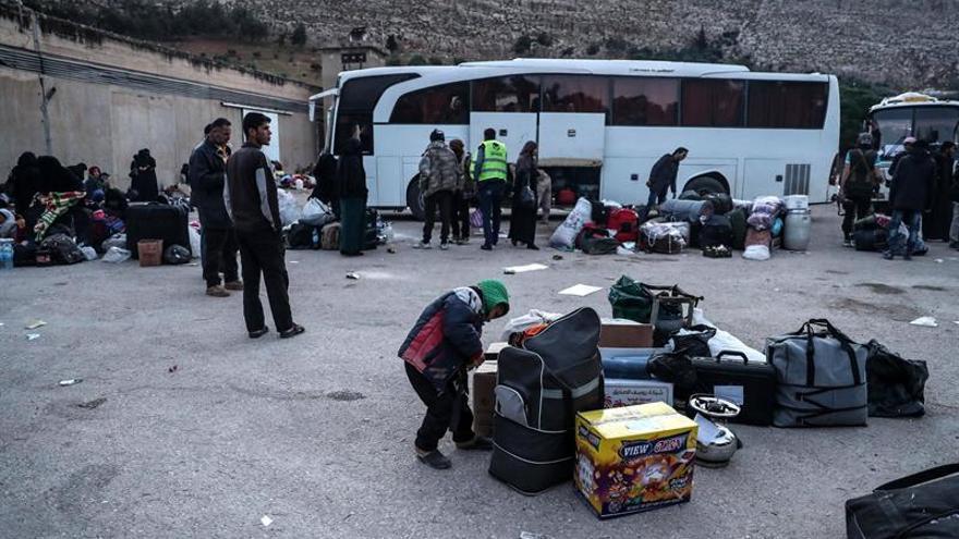 Un convoy de evacuados del centro de Siria se dirige hacia el norte tras un retraso